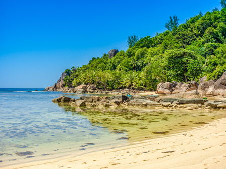 Beautiful tropical landscape of a sandy beach with boulders and green hills, on the shores of the Indian Ocean, Seychelles Standard-Bild - 126089718