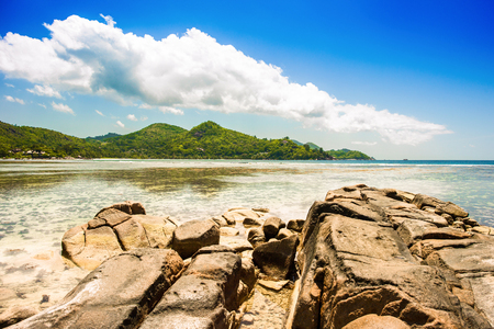 Beautiful tropical landscape of a sandy beach with boulders and green hills, on the shores of the Indian Ocean, Seychelles Standard-Bild - 126089721