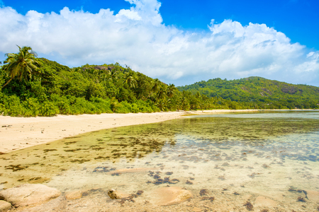Beautiful tropical landscape of a sandy beach with boulders and green hills, on the shores of the Indian Ocean, Seychelles Stok Fotoğraf