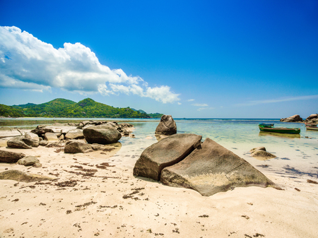 Beautiful tropical landscape of a rocky beach with boulders and green hills, on the shores of the Indian Ocean, Seychelles