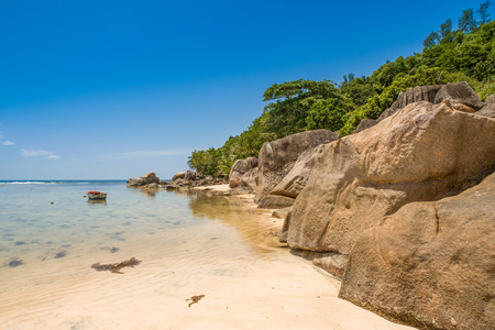 Beautiful tropical landscape of a rocky beach with boulders and green hills, on the shores of the Indian Ocean, Seychelles Standard-Bild - 126089775