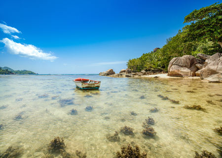 Beautiful tropical landscape of a sandy beach with boulders and green hills, on the shores of the Indian Ocean, Seychelles Standard-Bild - 126089776