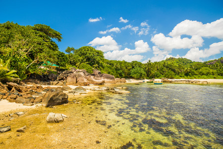 Beautiful tropical landscape of a rocky beach with boulders and green hills, on the shores of the Indian Ocean, Seychelles Standard-Bild - 126089784