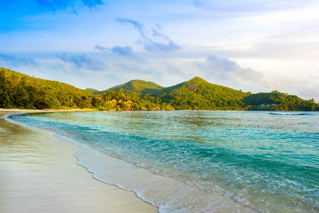 Beautiful tropical sunset landscape with green hills on the shores of the Indian Ocean, Seychelles