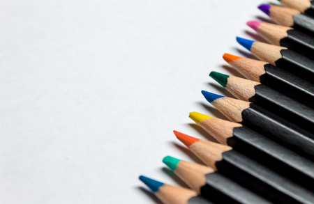 Colored pencils across white paper Stock Photo
