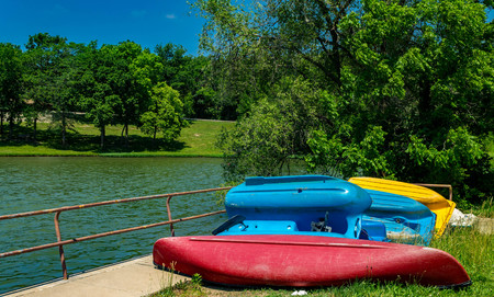 Old paddle boats and a canoe by the lake Stock Photo
