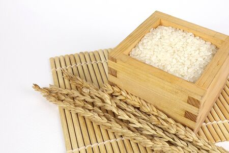 Japanese rice in a wooden box and grains of rice on the White Blackground.