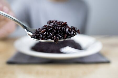 Riceberry in a spoon held by a man. Close up shot.