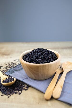 Riceberry cooked in a wooden cup with wooden spoons and forks placed on fabric.  And riceberry seeds in a wooden spoon. Top view. Low angle.