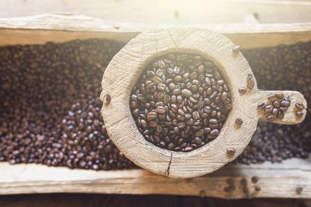 Coffee beans in a wooden vintage storage on coffee bean pile background.