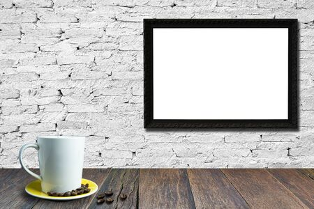 White coffee cup on wooden table, White brick wall background with empty black picture frame for text.