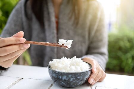 Asian women holding cooked jasmine rice bowls with chopsticks. Wearing a gray sweater.