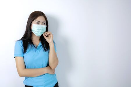 Asian women wear masks to prevent disease covid 19, long haired-black women. Wearing a blue collar shirt. Woman holding hands with a mask on white background.