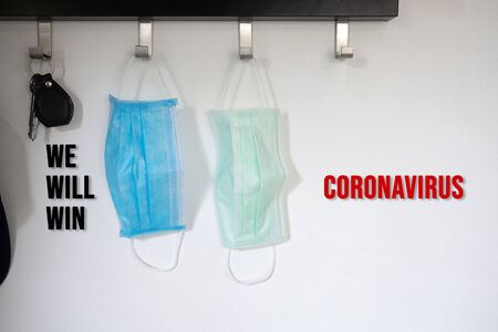 Two sanitary masks white and blue color and key hanging on the hook. with a message for WE WILL WIN CORONAVIRUS.