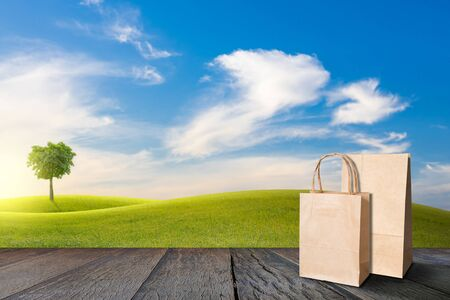 Recycle paper bag on old wooden floor beside green field on slope and tree with blue sky and clouds background.