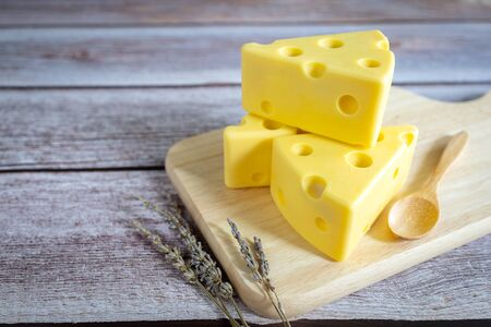 Three cheese on wooden tray on rustic wooden table.