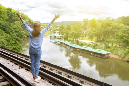 A woman standing on a railroad by the big river. Feel excited and happy on holiday. Vacation concept. Zdjęcie Seryjne