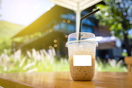 Cold coffee mug with white label for logo blurred coffee shop background.
