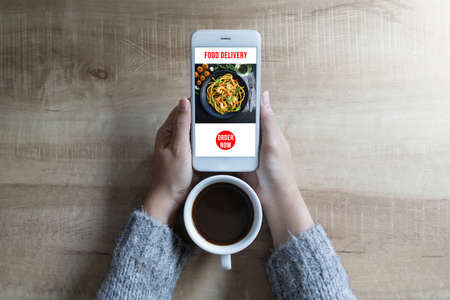 Woman's hands holding smartphone with application delivery food online and coffee cup. Concept food delivery.