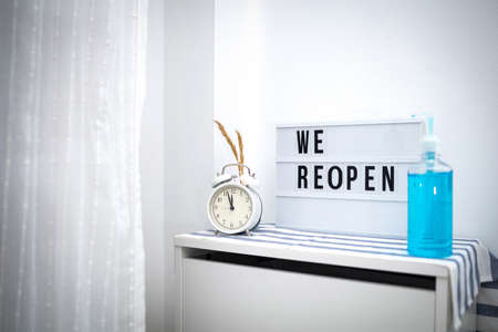 Words WE REOPEN and reopening on the light box and vintage alarm clock and Hand washing gel bottle. New life, new business, new deals concept.