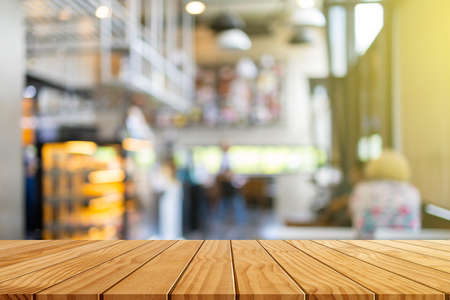Wooden table in front of blurred coffee shop background with bokeh for background usage. Foto de archivo