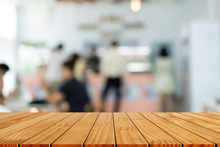 Wood table top with blur of people in coffee shop background. For montage product display or design key visual layout. Фото со стока