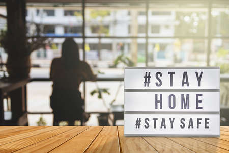 Lightbox sign with text hashtag #STAY HOME and #STAY SAFE with woman shadow, blurred coffee shop background. COVID-19. Stay home save concept.
