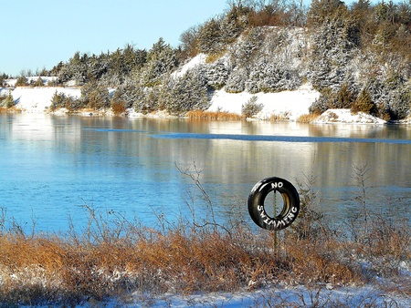 no swimming sign: A no swimming sign in front of a snowy lake