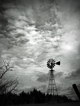 This black and white image features a lonely old-fashioned windmill beneath a cloudy sky.