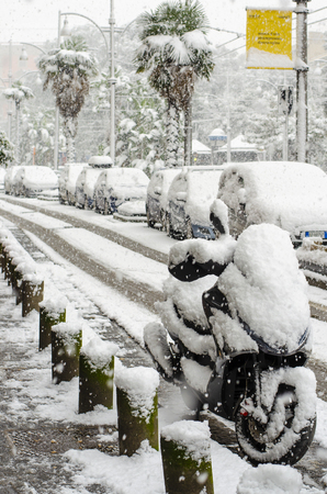 Motorcycle covered with snow standing on the road. Incredible atmospheric phenomenon in Naples. South italy Stock Photo