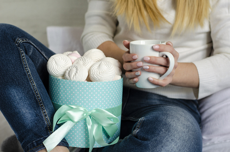 Female hands holding a white mug with latte coffee . Marshmallows amd meringues in a box. Life style concept. Close up Foto de archivo