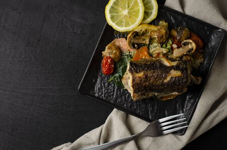 Grilled or oven baked hake fish on black plate. Keta diet and diet food concept. Healthy eating. Top view. Copy space. Stock Photo