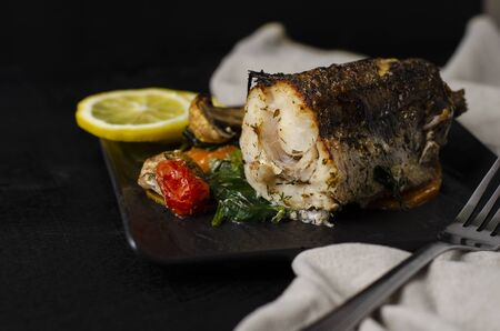 Grilled or oven baked hake fish on black plate. Keta diet and diet food concept. Healthy eating. Copy space