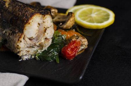 Grilled or oven baked hake fish on black plate. Keta diet and diet food concept. Healthy eating. Close up, copy space.