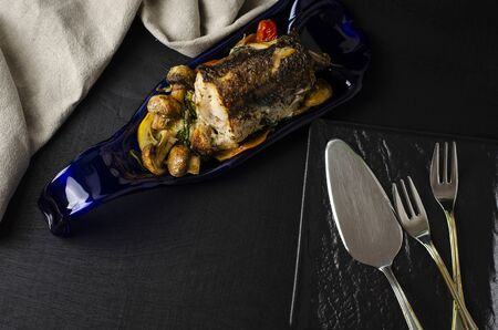 Roasted hake fish with vegetables on a blue plate on black background. Healthy eating and keto diet concept. Top view. Copy space Stock Photo