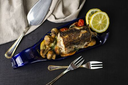 Baked piece of hake fish in the oven with vegetables on a blue plate made from bottle on black background. Healthy eating and keto diet concept. Top view