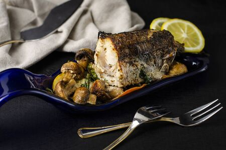 Baked piece of hake fish in the oven with vegetables on a blue plate made from bottle on black background. Healthy eating and keto diet concept. Copy space