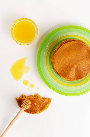 Top view of pumpkin pancakes on white background. Healthy tasty breakfast. Vertical