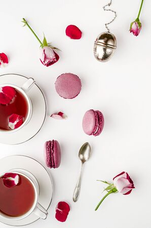 Breakfast tea on white table with roses and macaroons for two. Vallentines day and romance concept. Flat lay, top down