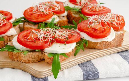 Panini aperti con mozzarella fresca, pomodori e rucola. Concetto di cibo italiano Archivio Fotografico