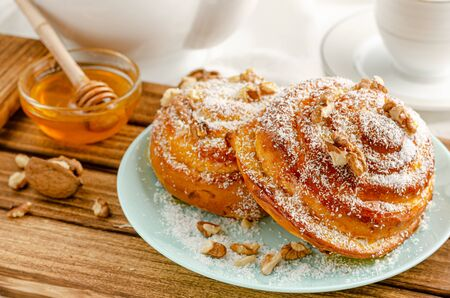 Traditional Swedish bakery or kanelbulle with walnuts on wooden tray. Breakfast or snack concept. Close up Banco de Imagens