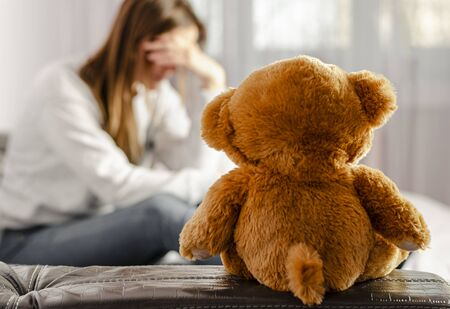 Selected focus on brown teddy bear sitting on depressed and pensive woman background. Infertility and divorce concept