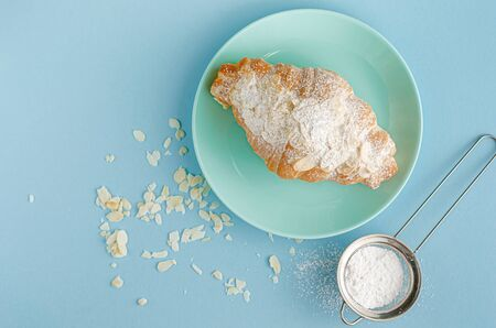 Homemade freshly baked croissant with powdered sugar and almond flakes on blue background. Copy space, flat lay. Stock Photo