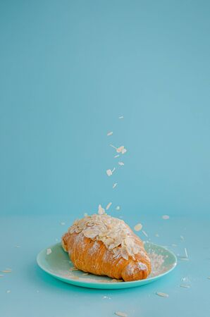 Falling almond flakes on freshly backed croissant on blue background. Copy space, vertical.