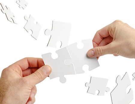 Couple of hands holding jigsaw puzzle isolated on white. Teamwork and business collaboration concept.