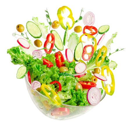 Fresh vegetable salad in transparent bowl with flying ingredients isolated on white. Proper nutrition.