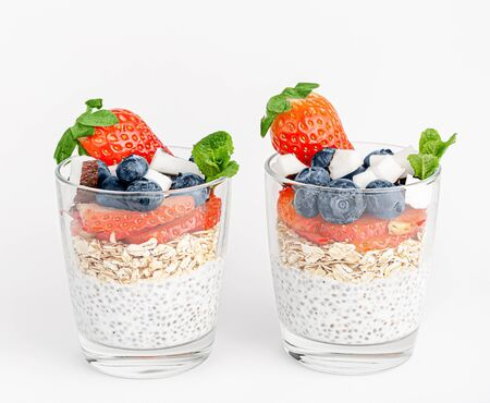 Chia pudding with oats, coconut, strawberry and blueberry on white background. Healthy food
