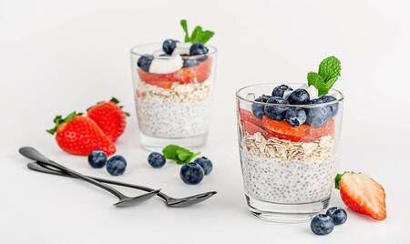 Chia pudding with oats, coconut, strawberry and blueberry on white background. Breakfast dessert