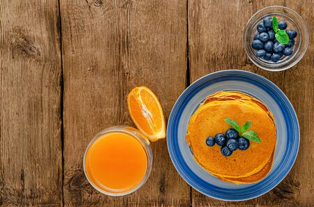 Pumpkin pancakes with blueberries and orange juice on rustic wooden background. Copy space. Overhead Фото со стока
