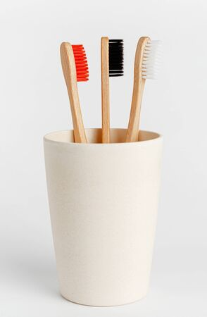 Red, white and black bamboo toothbrushes in eco cup on white background.